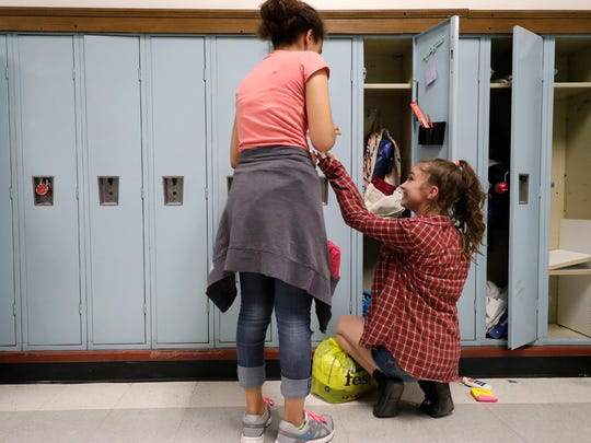 Seventh grade student Melonie Pinkney, left, helps Videl Martin clean out her locker Thursday at Roosevelt Middle School in Appleton.