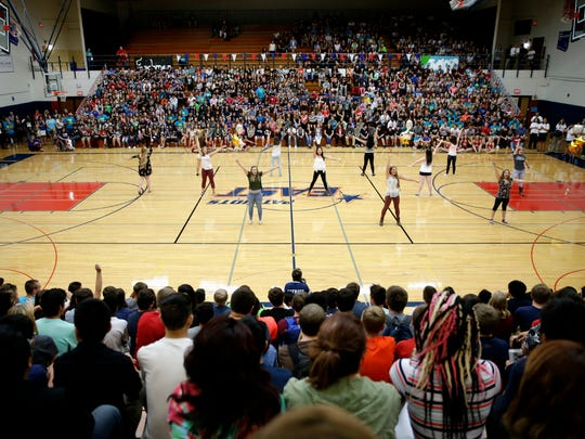 The Appleton East High School cheerleading squad runs through cheers with the school during a pep rally celebrating the first day of school and East's 50th anniversary Thursday, Sept. 1, 2016.