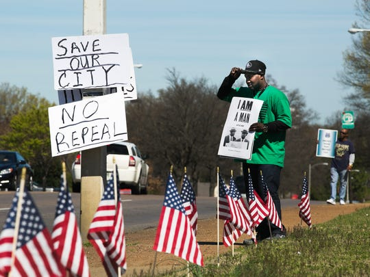 An American Federation of State, County and Municipal Employees (AFSCME) Local 1733 representative, who didn't want to provide his name, adjusts his cap during a unions protest, at the intersection of Poplar and Highland on Saturday.