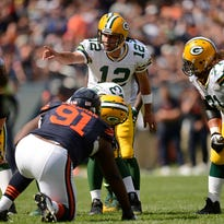 Green Bay Packers quarterback Aaron Rodgers (12) shouts instructions to his teammates at the line of scrimmage during the season against the Chicago Bears at Soldier Field.