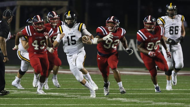 Neville quarterback Payton Batteford (15) finds a hole through the West Monroe defense on Saturday night at Bayou Jamb. The Rebels beat the Tigers 23-6.