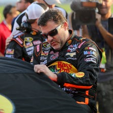 Tony Stewart climbs into his car prior to the start of the Oral-B USA 500 Saturday at Atlanta Motor Speedway.