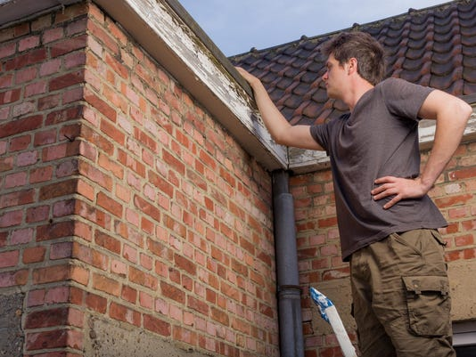 Young man inspecting the roof of an old house
