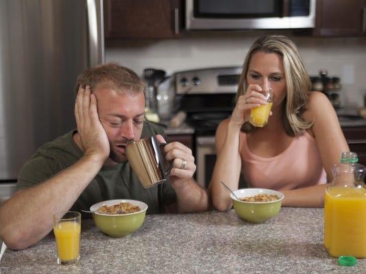 Exhausted couple has breakfast