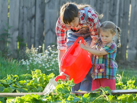 Woman helping her daughter to pour cucumbers