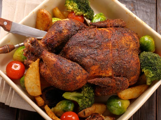 Whole roast chicken with vegetables in bowl