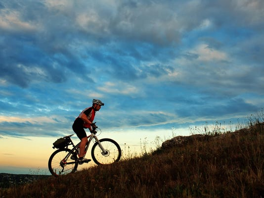 Silhouette of a biker and bicycle on sky background