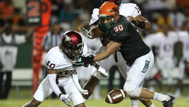FAMU's Elijah Price knocks the ball away from NC Central's David Miller during their Thursday night game at Bragg Memorial Stadium.