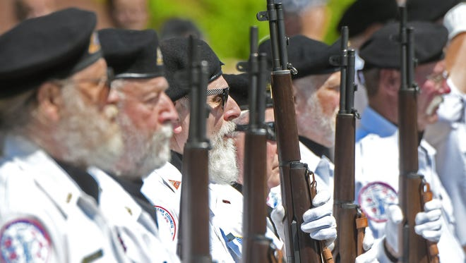 Members of the Joint Veterans Burial Squad of Richland County stand at attention as Taps is played at the conclusion of the Memorial Day ceremony in downtown Mansfield on Monday.
