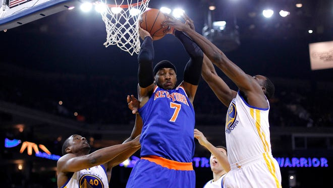 New York Knicks forward Carmelo Anthony (7) grabs a rebound against the Golden State Warriors in the first quarter at Oracle Arena.