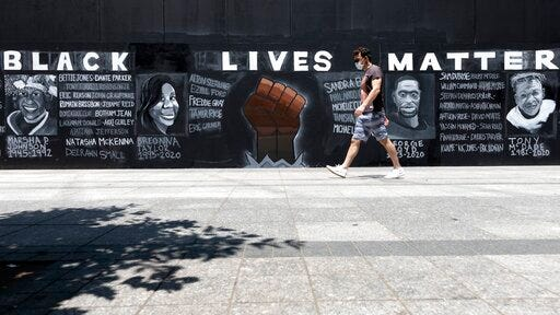 "FILE - In this June 6, 2020, file photo, a man walks past a ""Black Lives Matter"" mural painted on the boarded-up Apple Store, in Boston. Black Lives Matter has gone mainstream -- and black activists are carefully assessing how they should respond."