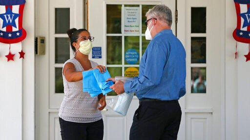 Brendan Williams, president of the New Hampshire Health Care Association, right, is handed gowns and masks which were received in a shipment from the federal government, by an employee at the Webster at Rye senior care center on Wednesday, July 1, 2020, in Rye, N.H. Isolation gowns with no sleeve openings for hands, child-sized gloves and surgical masks with ear loops that break when stretched make up the bulk of the personal protective equipment recently sent by the Federal Emergency Management Agency to New Hampshire nursing homes, according to Williams. The facility is not using the items they received from FEMA.