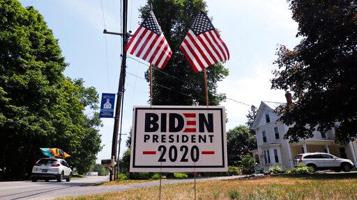 FILE - In this June 23, 2020, file photo, a car passes a yard displaying a campaign sign for Democratic presidential candidate, former Vice President Joe Biden in North Hampton, New Hampshire. The coronavirus pandemic isn't going away anytime soon, but campaigns are still forging ahead with in-person organizing. The pandemic upended elections this year, forcing campaigns to shift their organizing activities almost entirely online and compelling both parties to reconfigure their conventions.