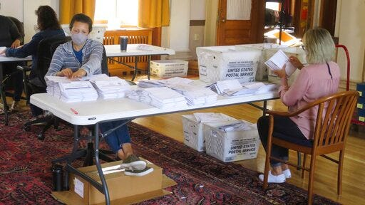 Election workers process absentee ballots for the primary elections in Portland City Hall on Friday, July 14, 2020 in Portland, Maine. Voters had been encouraged to vote via mail-in absentee ballots ahead of the election on Tuesday, July 14.