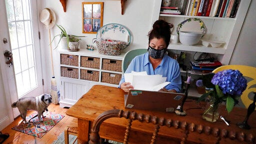 "Poet Tammi Truax looks over her recent work, as her pug ""Pie"" looks on, while seated at her writing table, wearing a protective mask due to the COVID-19 virus outbreak, Wednesday, July 29, 2020, at her home in Eliot, Maine. Truax, the poet laureate for Portsmouth, N.H., pens a weekly pandemic poem that is included in the city's COVID-19 newsletter."