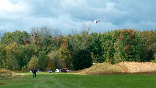 In this photo provided by Spectrum News Buffalo, a helicopter circles the site of a small plane crash near Pembroke N.Y., Friday, Oct. 2, 2020. Two people aboard the aircraft died.