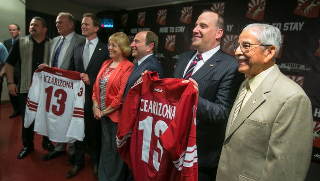 NHL Commissioner Gary Bettman, middle, poses with Coyotes owners George Gosbee, middle left, and Anthony LeBlanc, second from right, along with Glendale City Council members during a press conference in 2013.