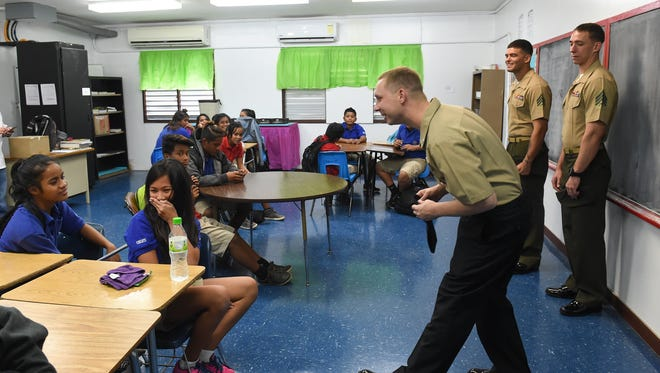 Navy Petty Officer 2nd Class Andrew Hess attempts to get a question out of an Oceanview Middle School student during a USS America port visit on Jan. 8, 2018.