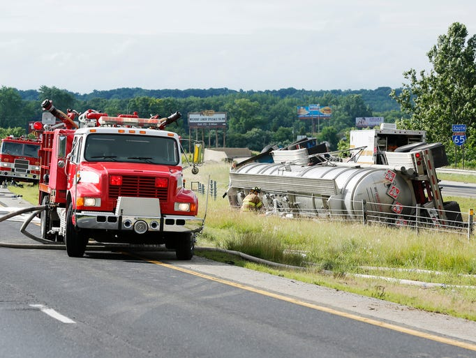 Firefighters respond after a tanker hauling heptane overturned in the southbound lane of I-65 Thursday, July 3, 2014, just south of the Ind. 43 exit near Battle Ground. Sgt. Kim Riley of Indiana State Police said traffic in both lanes of I-65 would be closed until the highly flammable material can be cleaned up.