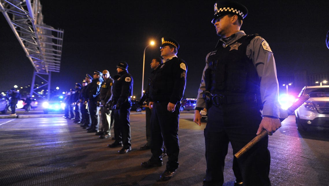 Police officers form a line to prevent protesters from