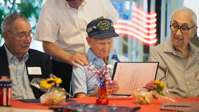 """""""I miss my friends,"""" said David Goldsboro, center, of his fellow World War II Navy veterans. Goldsboro was among 12 WWII veterans honored Sunday by residents of Forest Park Mobile Home Park in North Fort Myers. The veterans were given certificates of appreciation, U.S. Flag lapel pins, quilts and other items. The event was hosted by the Forest Park Craft Club with assistance from the Honor Guard for Hope HealthCare."""