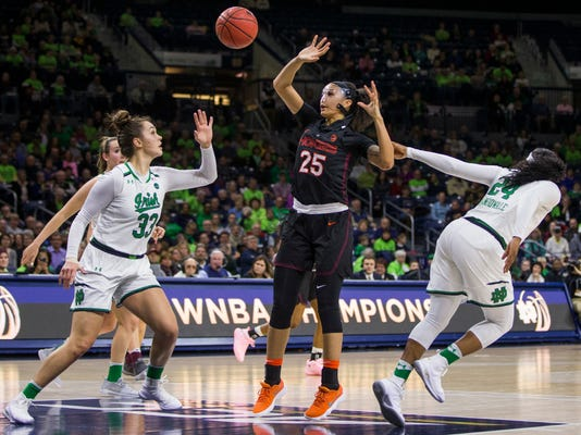 Notre Dame's Arike Ogunbowale (24) and Kathryn Westbeld (33) work together to steal the ball from Virginia Tech's Alexis Jean (25) during the first half of an NCAA college basketball game Thursday, Feb. 22, 2018, in South Bend, Ind. (AP Photo/Robert Franklin)