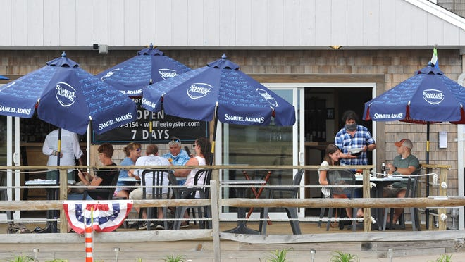 """Late afternoon diners were more interested in being outside at the Bookstore & Restaurant in Wellfleet even as indoor seating was again allowed as of Monday with safety precautions. """"People are still nervous about the coronavirus,"""" owner Caroline Parlante said."""