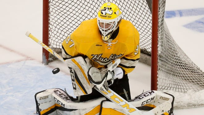 Michigan Tech's goalie Angus Redmond makes a save during the second period of Michigan Tech's 5-2 loss to Denver in the NCAA hockey tournament Midwest Regional semifinal Saturday in Cincinnati.