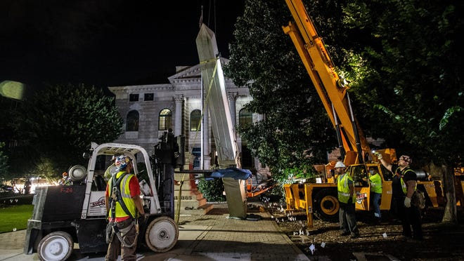 Workers remove a Confederate monument with a crane on Thursday, June 18, 2020, in Decatur, Georgia. The 30-foot obelisk in Decatur Square, erected by the United Daughters of the Confederacy in 1908, was order to be removed by a judge and placed in storage indefinitely.