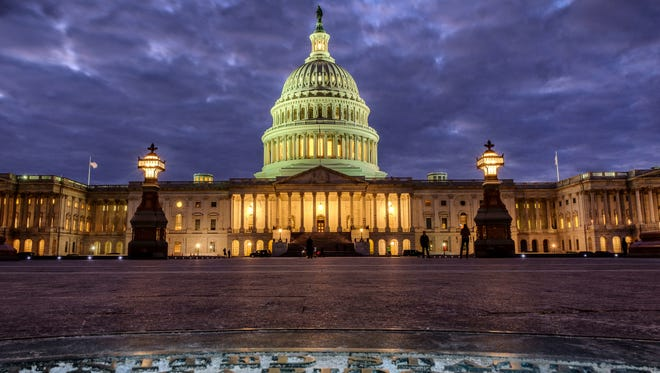 In this Jan. 21, 2018, photo, lights shine inside the U.S. Capitol Building as night falls in Washington.  President Donald Trump will deliver his first State of the Union address Tuesday night but, as always, lawmakers are angling to steal part of the spotlight. Many female Democratic lawmakers plan to follow the lead of celebs at this year's Golden Globe Awards by wearing black to the State of the Union.  (AP Photo/J. David Ake)