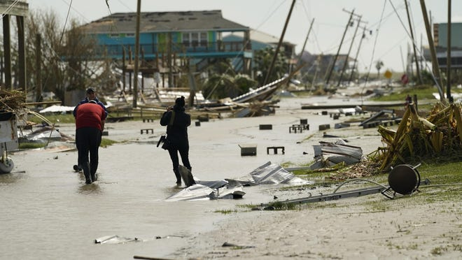 Journalists examine damage left in the wake of Hurricane Laura, Thursday, Aug. 27, 2020, in Holly Beach, La.