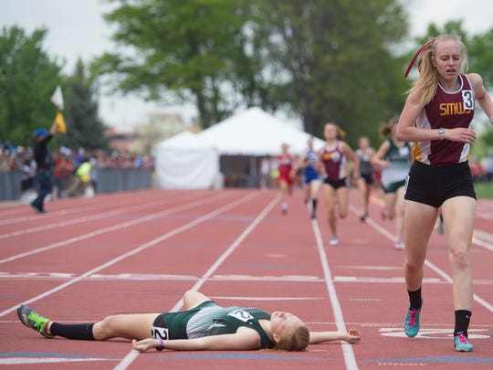 Leeann Wagner of Heritage Christian lays on the track after being the first to cross the finish line in the 1A 800-meter race during the CHSAA State Track and Field Championships at JeffCo Stadium in Lakewood on Friday.