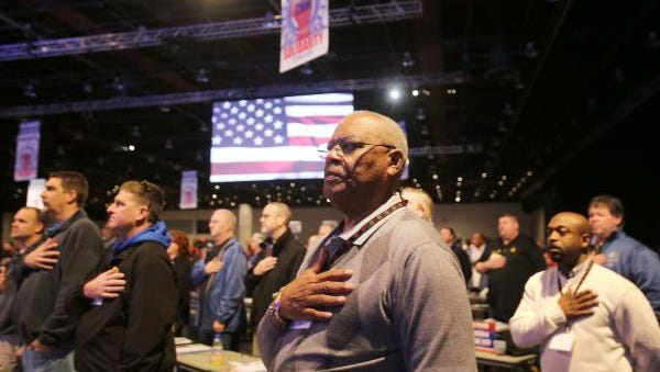 UAW members, including William Monroe of Atlanta, stand for the Pledge of Allegiance at the bargaining convention last week in Detroit.
