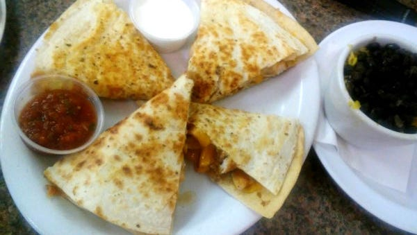Charlene's Coyote Grill's grilled chicken quesadilla with a side of beans and rice.