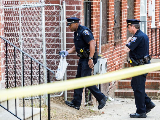 Officers investigate an alley after finding a bag and cell phone near the scene of a shooting in the 600 block of West Sixth Street in Wilmington on Sunday afternoon.