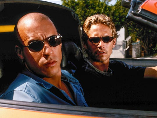 """June 23: Brian O'Conner (Paul Walker, right) goes undercover to bring down legendary street racer Dominic Toretto (Vin Diesel) in the original """"The Fast and the Furious"""" from 2001. © Universal Pictures"""