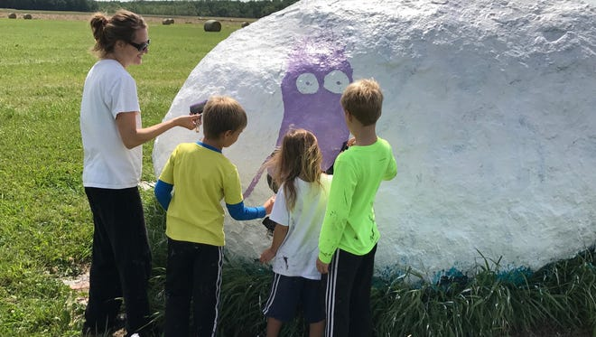 Lori Kozicki of Stevens Point and her children, from left, Jimmy, Liz and Joey, paint a minion character on a rock outside Rudolph on Wednesday, Aug. 9, 2017 in memory of her nephew, Wayland Villars, who died on Aug. 9, 2013.