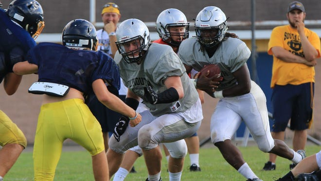 During a recent scrimmage, Plymouth running back Darius Timmons (right) follows the blocking lead of lineman Robert Florence.