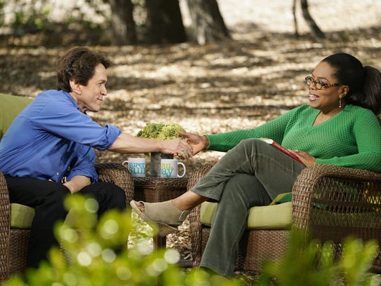 Mitch Albom shakes the hand of Oprah Winfrey on the