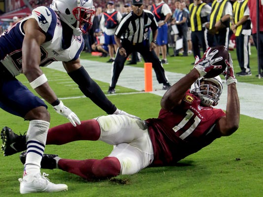 Arizona Cardinals wide receiver Larry Fitzgerald (11) catches his career 100th touchdown pass during the second half of an NFL football game as New England Patriots cornerback Logan Ryan (26) defends, Sunday, Sept. 11, 2016, in Glendale, Ariz. (AP Photo/Rick Scuteri)