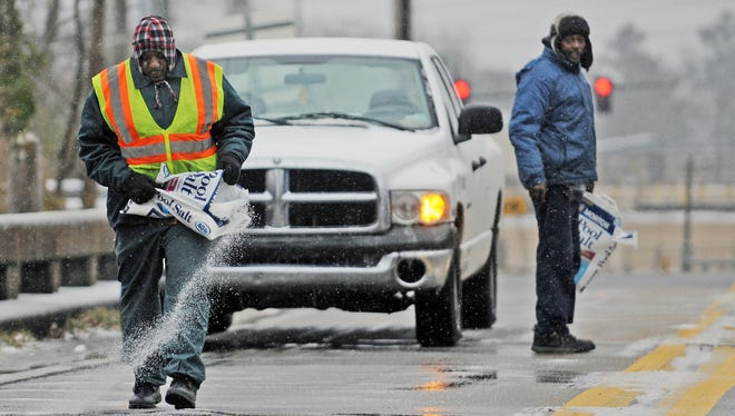 City employees spread salt along a bridge as patches of ice begin to form on Jan. 28, 2014, in Hattiesburg Miss.
