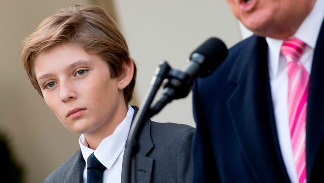 Barron Trump looks on President Trump (R) speaks during the turkey-pardoning ceremony in the Rose Garden of the White House Nov. 21, 2017.