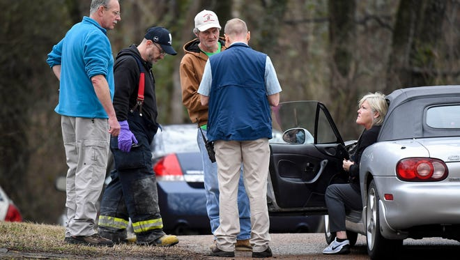 Friends talk with investigators outside the house where  three people were killed in a fire on Southwood Drive in Nashville, Tenn., Wednesday, Feb. 14, 2018.