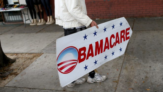 Pedro Rojas holds a sign directing people to an insurance company where they can sign up for the Affordable Care Act, also known as Obamacare, in Miami earlier this year.