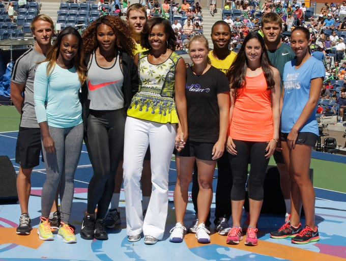 From left, Denis Kudla, Sloane Stephens, Serena Williams, Jack Sock, first lady Michelle Obama, center, Melanie Oudin, Donald Young, Christina McHale, Ryan Harrison, and Madison Keys,  pose for a photograph at the 18th Annual Arthur Ashe Kids Day.