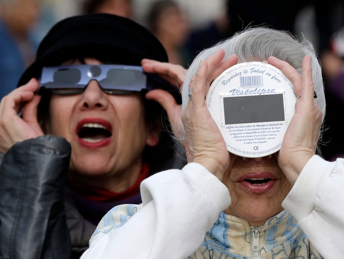 People view the solar eclipse darkening the sky Friday