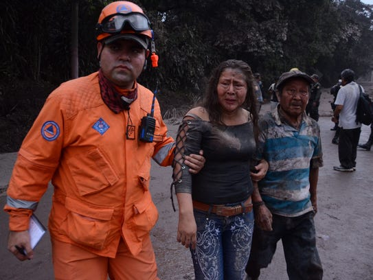 A worker from the National Coordinator for Disaster Reduction of Guatemala assists people in El Rodeo on June 3, 2018, after the eruption at Fuego volcano.
