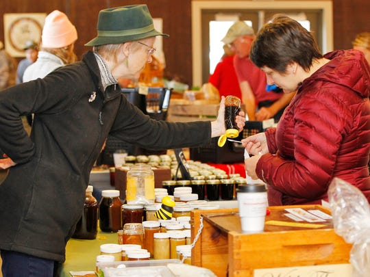 Owner Sue Garing squeezes a sample of honey to Julia