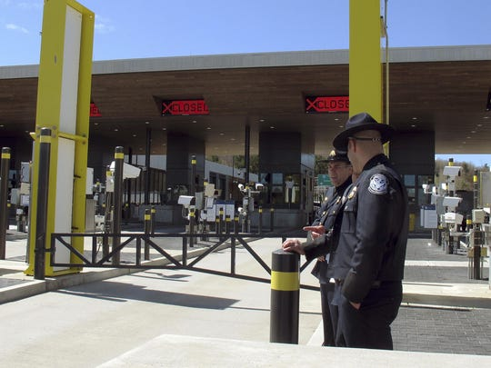In this May 8, 2019 photo, U.S. Customs and Border Protection officials stand at the new border crossing facility on the U.S.-Canadian border in Derby Line, Vt. Some along the northern U.S. border are worried the temporary transfer of hundreds of border agents south could cause backups of people seeking to enter the United States from Canada during the busy summer tourist season. (AP Photo/Wilson Ring)