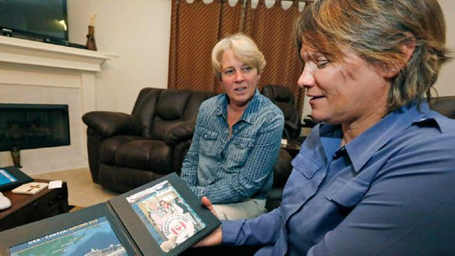 Lauren Czekala-Chatham, right, shows off a photograph of herself and partner Dawn Jefferies, left, at home in Hernando, Miss. Czekala-Chatham hopes Mississippi will recognize her same sex marriage performed in California, so she can get divorced.